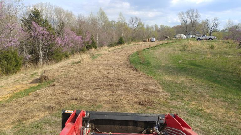 rutted farm road transformation.  It's been graded with the box blade, smoothed with the landscape rake and seeded with grass.
